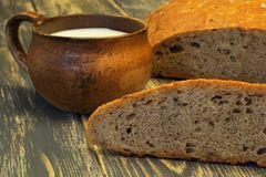Robić smakowita miękka fragrant rumiana gliny filiżanka z mlekiem na ciemnym naturalnym drewnianym tle i Przyschnięci przepisy obraz stock