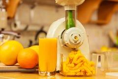 Robić sokowi pomarańczowemu w juicer maszynie w kuchni Zdjęcia Stock