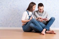 Robić zakupy online wpólnie Piękny młody kochający pary robić zakupy online podczas gdy siedzący na podłoga wpólnie Obraz Stock