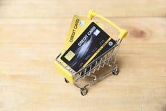 Robi? zakupy online z kart? kredytow? w w?zku na zakupy na drewnianym tle dla online zap?aty w domu obraz royalty free