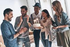 Robi życzeniu! Szczęśliwy młody człowiek odświętności urodziny wśród przyjaciół obrazy royalty free