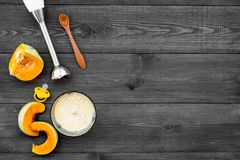 Robi dziecka jedzeniu w domu Puree z dyniowym pobliskim immersyjnym blender i pacyfikator na ciemnego drewnianego tła odgórnym wi zdjęcie stock