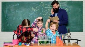 robi? eksperymentom z cieczami w chemii lab Chemii lab szcz??liwy dziecko nauczyciel tylna szko?y dzieciaki w lab ?akiecie zdjęcia stock
