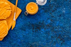 Robi grzance z dokrętki pastą Dwa toastes, nóż i szklany słój z dokrętki pastą, dokrętki na błękitnej tło kopii przestrzeni Obrazy Stock