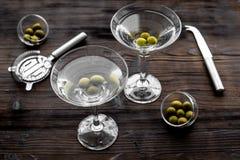 Robi Martini koktajlom Szkło z napojem, oliwkami i naczyniami na ciemnego drewnianego tła odgórnym widoku, Obraz Stock