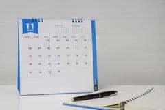 Robi notatce na notatniku z Listopadu kalendarzem Zdjęcie Stock