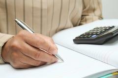 Robi notatce w notatniku zdjęcia royalty free