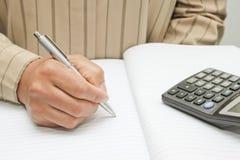 Robi notatce w notatniku fotografia royalty free