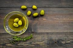 Robi oliwa z oliwek pojęciu Zielone oliwki w pucharze z oliwa z oliwek na ciemnej drewnianej tło odgórnego widoku kopii przestrze Fotografia Royalty Free
