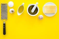 Robi pesto kumberlandowi Ser, czosnek, oliwa z oliwek, solankowy pobliski grater i moździerz na żółtej tło odgórnego widoku kopii Obrazy Royalty Free
