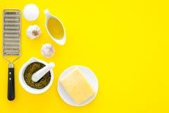 Robi pesto kumberlandowi Ser, czosnek, oliwa z oliwek, solankowy pobliski grater i moździerz na żółtej tło odgórnego widoku kopii Fotografia Stock