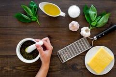 Robi pesto kumberlandowi Ser, czosnek, zielony basil, oliwa z oliwek, sól, grater pobliska ręka wali kumberland w mortatr na ciem Zdjęcie Royalty Free
