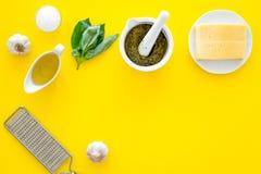 Robi pesto kumberlandowi Ser, czosnek, zielony basil, oliwa z oliwek, solankowy pobliski grater i moździerz na żółtego tła odgórn Obraz Stock