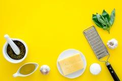 Robi pesto kumberlandowi Ser, czosnek, zielony basil, oliwa z oliwek, solankowy pobliski grater i moździerz na żółtego tła odgórn Zdjęcia Royalty Free