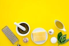Robi pesto kumberlandowi Ser, czosnek, zielony basil, oliwa z oliwek, solankowy pobliski grater i moździerz na żółtego tła odgórn Fotografia Royalty Free