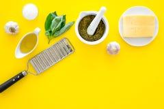 Robi pesto kumberlandowi Ser, czosnek, zielony basil, oliwa z oliwek, solankowy pobliski grater i moździerz na żółtego tła odgórn Zdjęcia Stock
