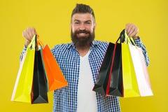 Robi robić zakupy radosnego Mężczyzny brodatego modnisia rozochocona twarz niesie papierowe torby na zakupy na żółtym tle enjoy obrazy stock