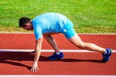 Robi wysiłkowi dla zwycięstwa Mężczyzna atlety biegacza stojaka początku pozycji stadium niska ścieżka Biegacz przygotowywający i fotografia stock