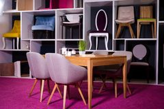 Robi zakupy, sprzedaż meble w centrum handlowym Ekspozyci próbka Łomota drewnianego stół z tkanin krzesłami w szarość na białej p Fotografia Royalty Free