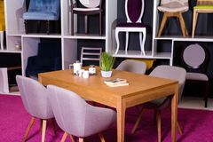 Robi zakupy, sprzedaż meble w centrum handlowym Ekspozyci próbka Łomota drewnianego stół z tkanin krzesłami w szarość na białej p zdjęcie royalty free