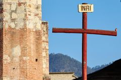 Robin perched on a cross. Robin perched on a wooden red catholic cross that is in front of the atrium of a church made of stone and brick royalty free stock photo