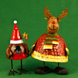 Robin and reindeer Christmas decorations. Pair of metal robin and Rudolph the red-nosed reindeer Christmas decorations on green Stock Images