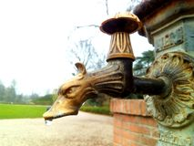 Robinet de fontaine avec une forme de tête de dragon en parc Image libre de droits