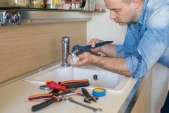 Robinet disjoint de fixation d'homme dans la cuisine photos stock