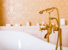 Robinet riche d'or et bain blanc dans la salle de bains Photographie stock