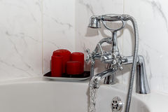 Robinet/robinet de salle de bains de vintage avec les bougies rouges Photographie stock