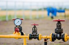 Robinets rouges avec le tuyau d'acier dans l'installation de traitement de gaz naturel photographie stock libre de droits