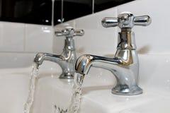 Robinets sur le baquet de bain avec l'eau courante Image stock