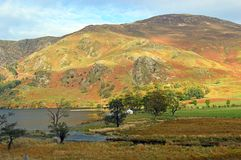 Robinson Fell and white farmhouse viewed from Buttermere. In the autumn. The Lake District National Park, Cumbria, United Kingdom royalty free stock image