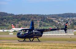 Robinson R44 korpsvart helikopter II i den Zurich flygplatsen Royaltyfri Foto