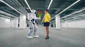 Robot amical gifting les tulipes rouges à une jeune femme banque de vidéos