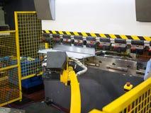 Operator bending metal sheet by sheet bending machine. Robot arm bending metal sheet by sheet bending machine, cnc control metal sheet bending machine, high Royalty Free Stock Photos