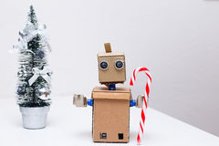Robot with arms and Christmas decorations on the table. Robot with arms and Christmas decorations stock images