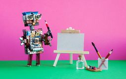 Robot artist with brush paints palette, wooden easel and blank white paper. Advertising poster mockup. Pink background.  royalty free stock photos