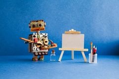 Robot artist with brush paints palette, wooden easel and blank white paper. Advertising poster studio school of visual Royalty Free Stock Images
