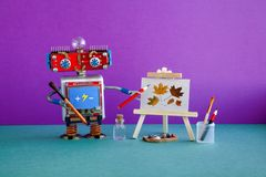 Robot artist pencil hand, wooden easel still-life artwork autumn leaves. Advertising poster studio school of visual arts. And drawing. Artist`s tools palette royalty free stock photography