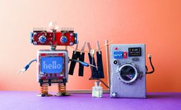 Robot automation laundry room. Robotic washer with message Hello. Silver washing machine, men`s jeans pants dried on. Clothesline with clothespins. pink violet royalty free stock images