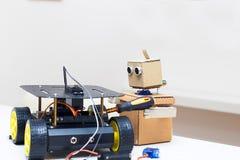 Robot avec des mains réparant le robot sur des roues Photographie stock