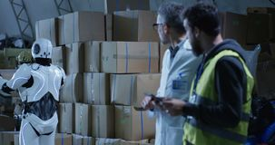 Robot bringing box to technicians in a warehouse. Medium long shot of robot bringing a box to technicians in a warehouse stock footage