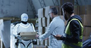 Robot bringing box to technicians in a warehouse. Medium long shot of robot bringing a box to technicians in a warehouse royalty free stock photo