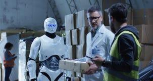 Robot bringing box to technicians in a warehouse. Medium long shot of robot bringing a box to technicians in a warehouse royalty free stock photos