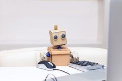 Robot che funziona ad un computer e ad un topo usato di e alla tavola Immagini Stock