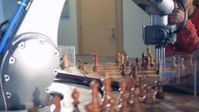 Robot che gioca scacchi con un essere umano Il manipolatore della mano del computer muove gli scacchi e preme il tasto dell'orolo archivi video