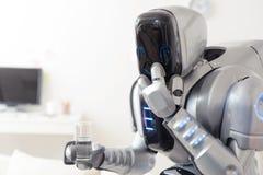 Robot che tiene bicchiere d'acqua fotografie stock libere da diritti