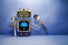 Robot chef with ladle skimmer and message Let`s cook. Creative design robotic toy holds kitchen utensils on blue royalty free stock image