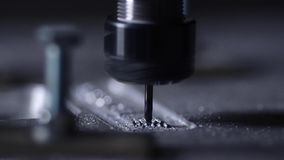 The robot in the company with the help of a program written to work with steel is cut from an aluminum plate with a. Drill in slow motion. Metal shavings fly in stock footage